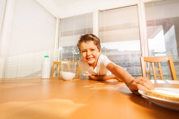 Smiling kid boy making a long arm for sandwich stock photo
