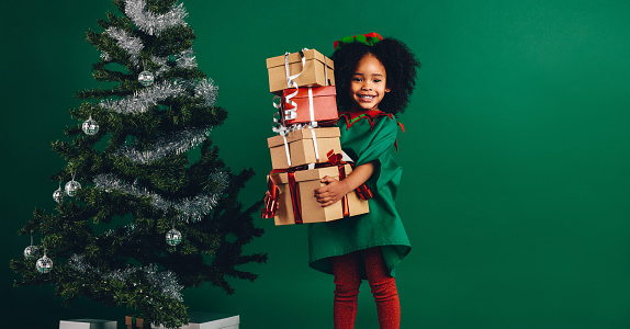 Smiling kid holding a pile of gift boxes