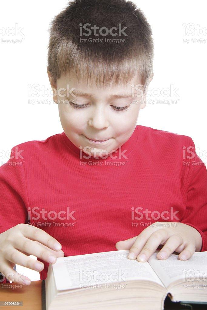 Criança sorridente em vermelho lendo livro na mesa foto royalty-free