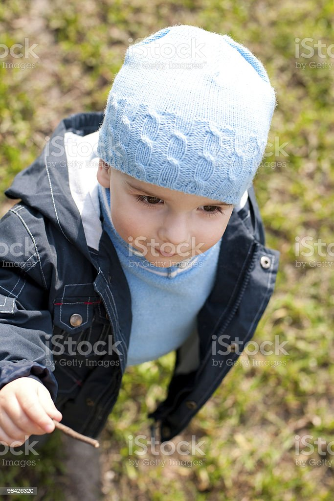 Smiling kid is playing with a stick while walking outside royalty-free stock photo