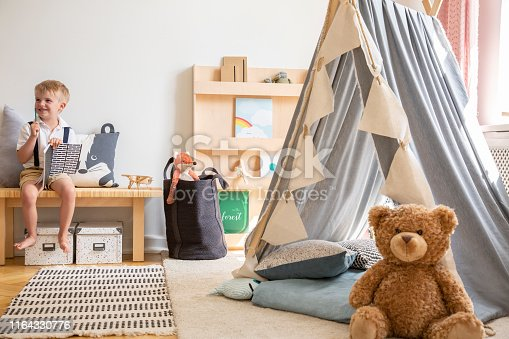 istock Smiling kid sitting on bench with notebook, real photo of natural playroom interior with scandinavian tent and teddy bear 1164330776