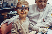 istock Smiling kid with magnifying eyeglasses in IT lab. 1200991556