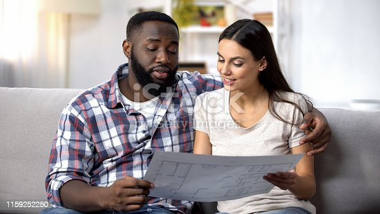 Smiling lady and black man planning interior design of new house, crediting