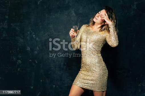 Celebration party, holiday, fun. Happy young woman celebrating. Attractive smiling lady in cocktail dress drinking champagne
