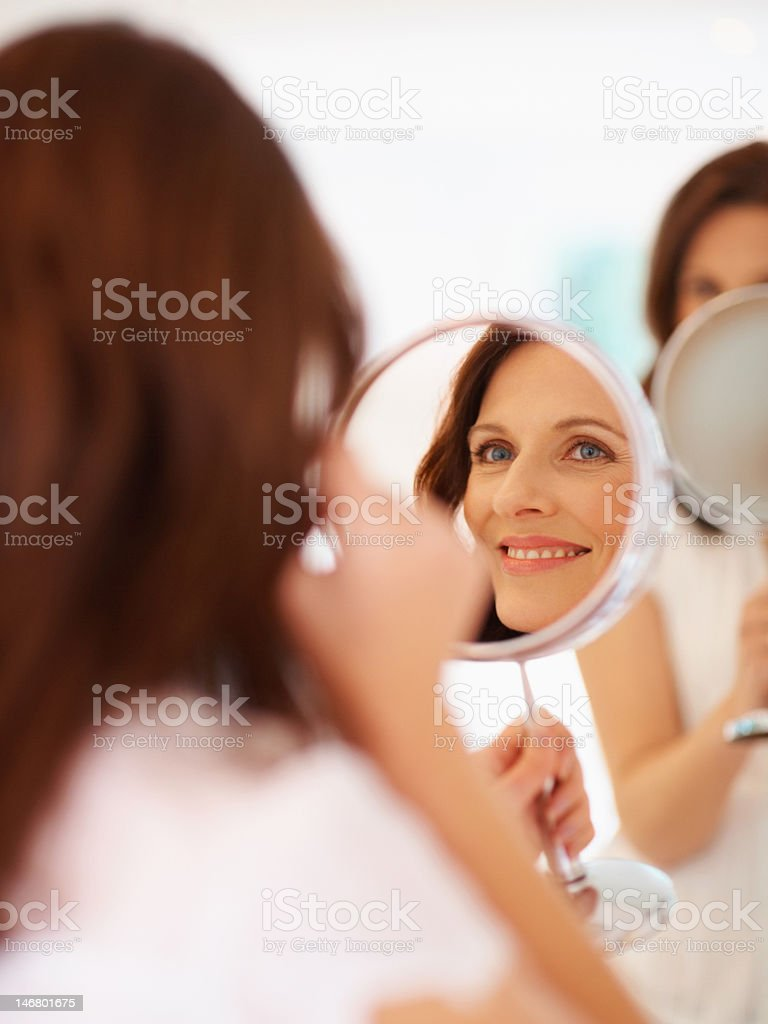 Smiling lady looking at her face in mirror stock photo
