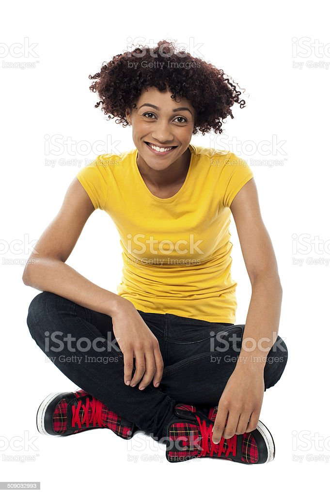 Smiling lady sitting legs crossed on the floor stock photo