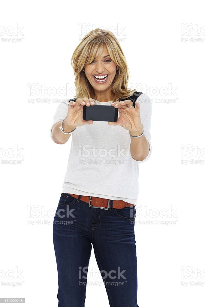 Smiling lady taking your picture with her cell phone royalty-free stock photo