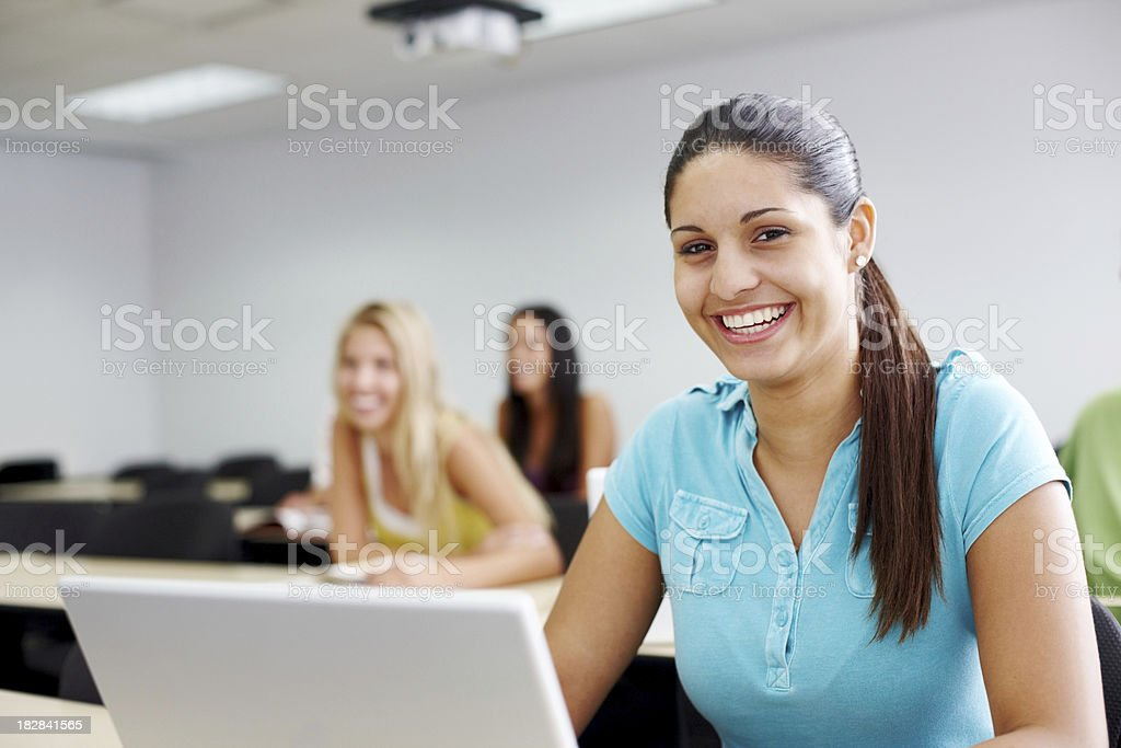 Smiling lady using laptop with friends in the background royalty-free stock photo