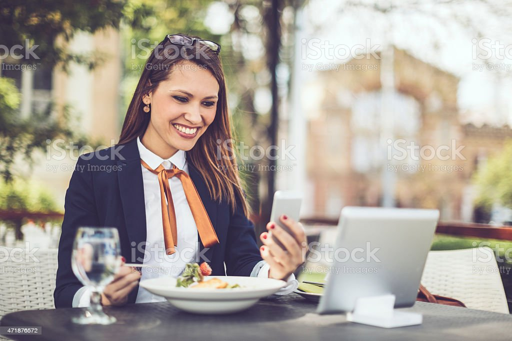Smiling Latin businesswoman text messaging stock photo