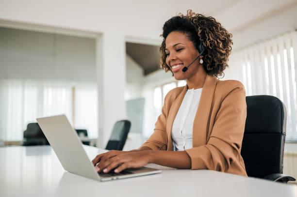 Una mujer de negocios latina sonriente trabajando con portátil y auriculares, retrato. Alegre asistente en la luminosa oficina. - foto de stock