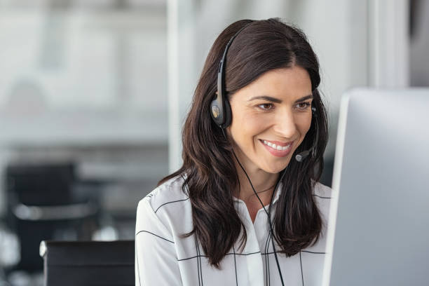Smiling latin woman in call center stock photo