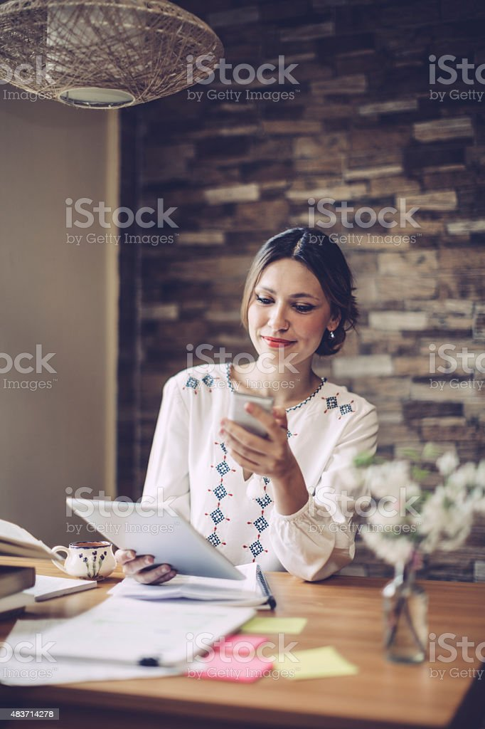 Smiling latin woman texting stock photo