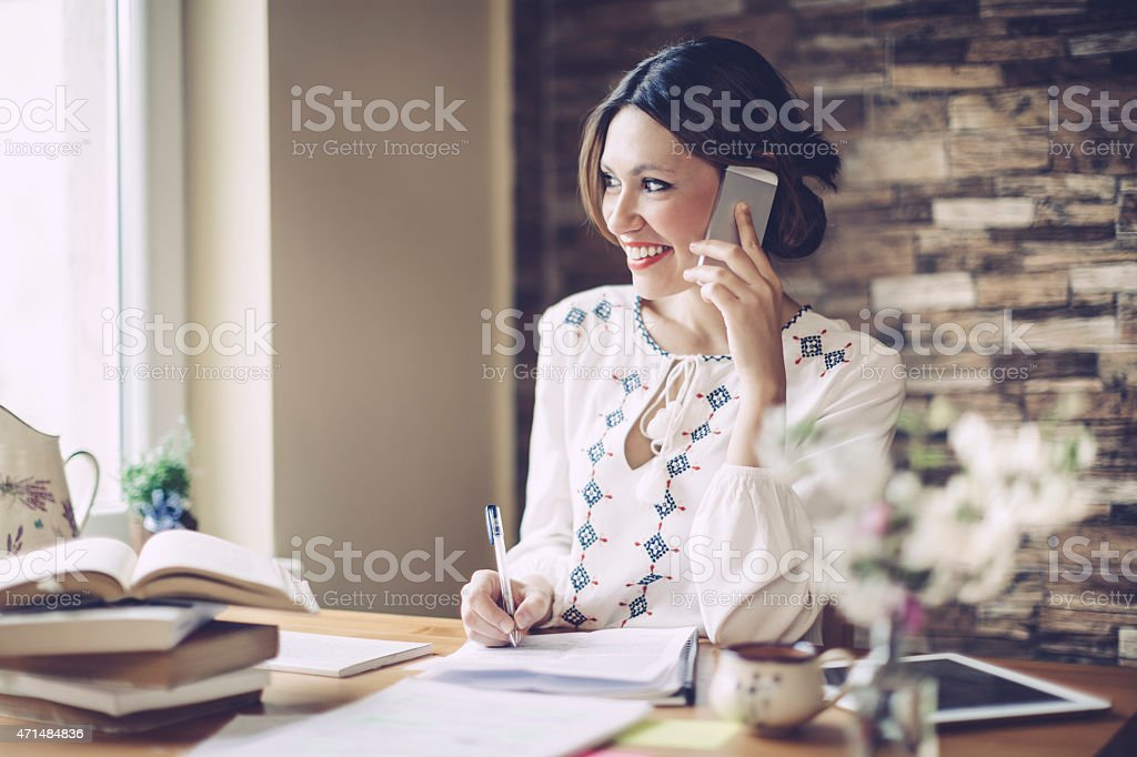 Smiling latin woman working at home stock photo