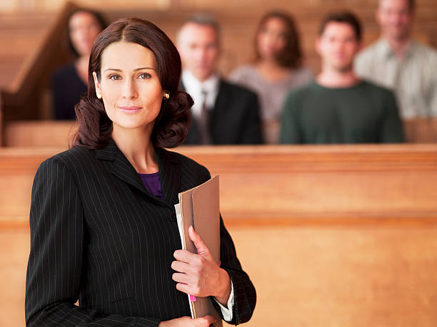 Smiling lawyer holding file in courtroom stock photo