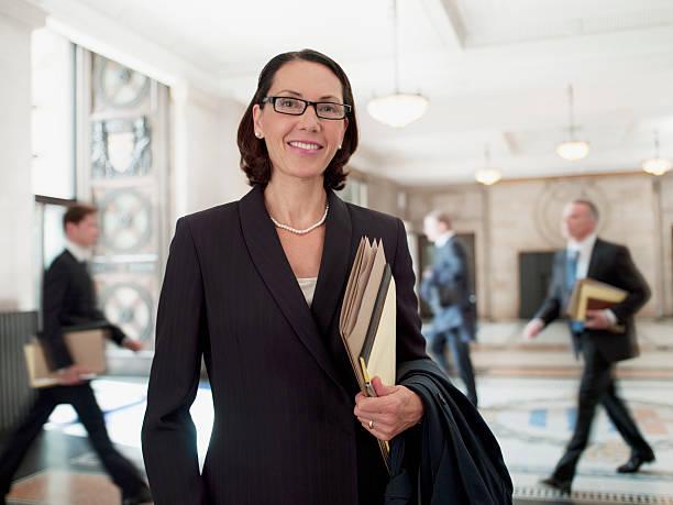 smiling lawyer in lobby - four lawyers stockfoto's en -beelden