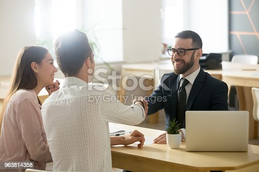 963814372istockphoto Smiling lawyer or financial advisor handshaking senior couple at meeting 963814358