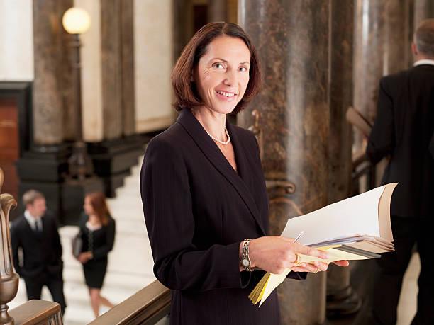 smiling lawyer reviewing case file in corridor - four lawyers stockfoto's en -beelden
