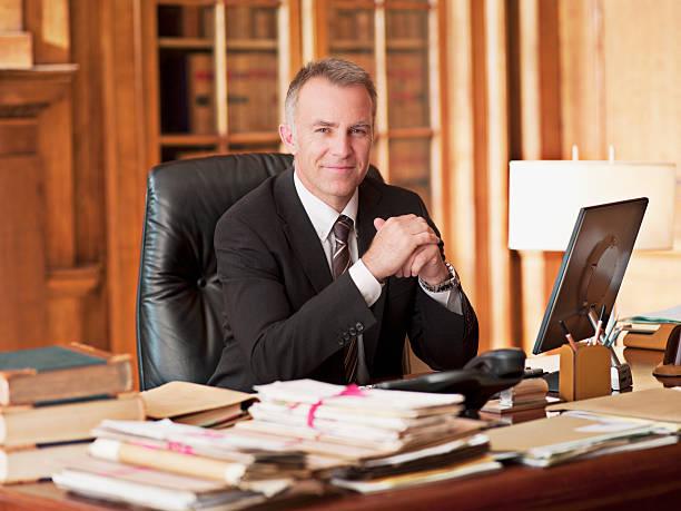 sonriendo abogado sentado en el escritorio de oficina - abogado fotografías e imágenes de stock