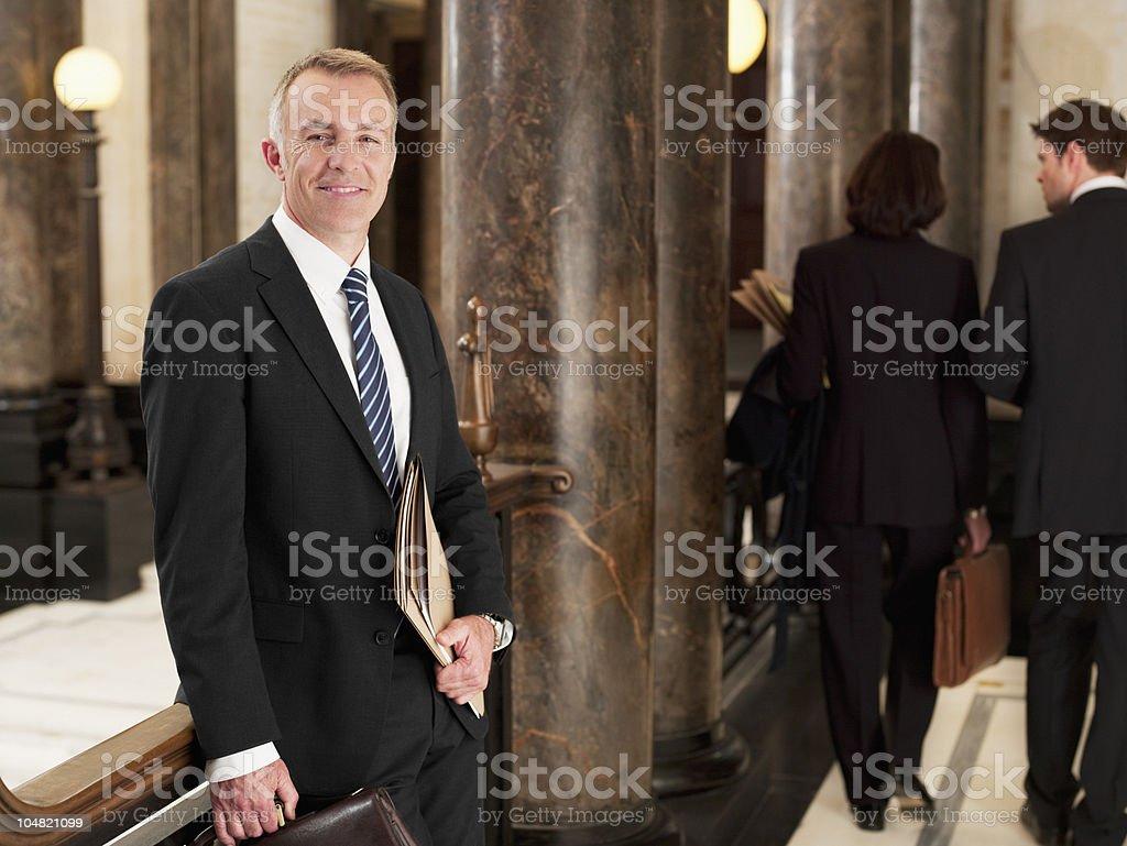 Smiling lawyer standing in corridor stock photo