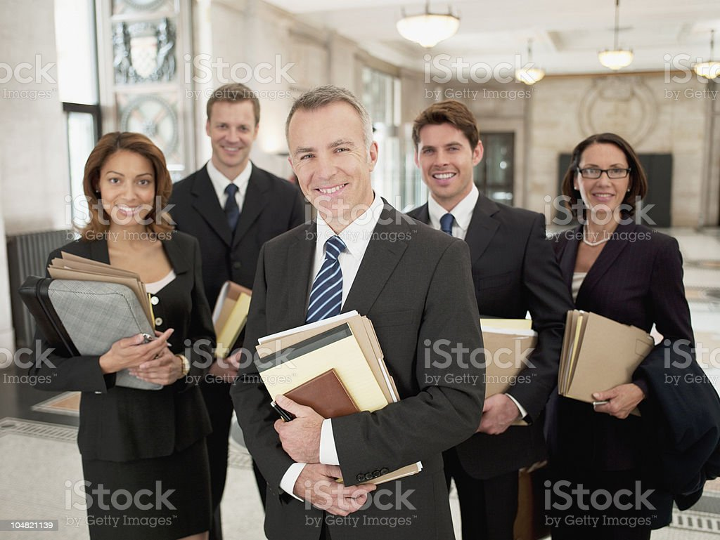 Smiling lawyers holding files in lobby stock photo