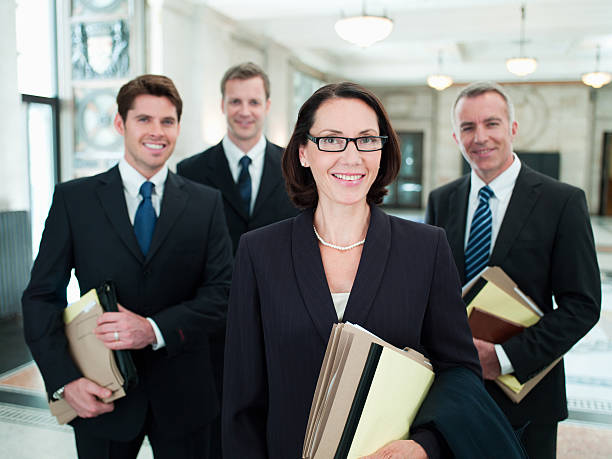 smiling lawyers holding files in lobby - four lawyers stockfoto's en -beelden