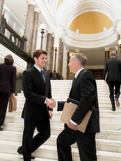 smiling lawyers shaking hands on stairs - four lawyers stockfoto's en -beelden