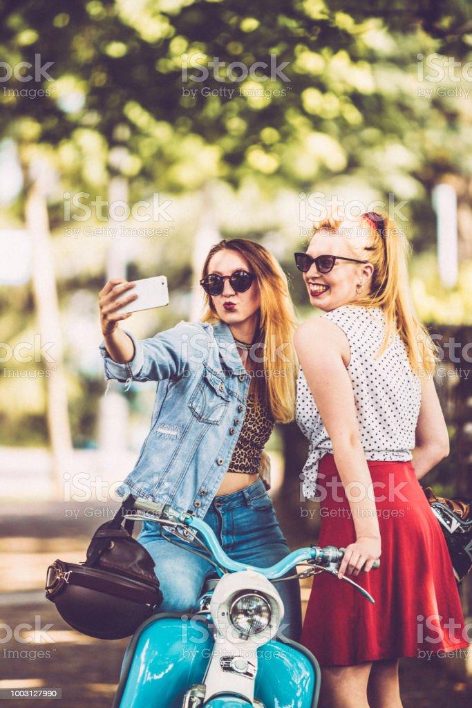 Smiling Lesbian Couple Taking A Selfie On City Street