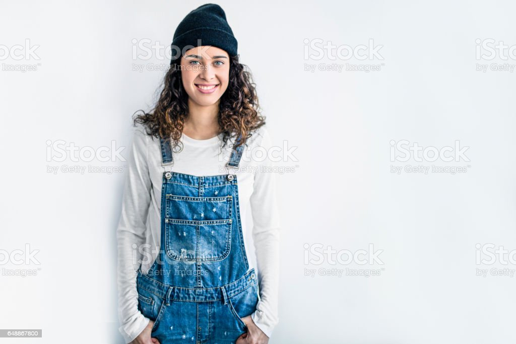Smiling lesbian standing against white wall stock photo