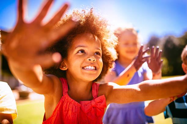 Smiling little Afro girl holding up her hands happily stok fotoğrafı