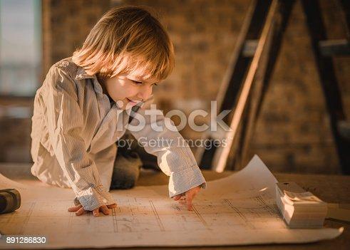 istock Smiling little architect examining blueprints on construction site. 891286830