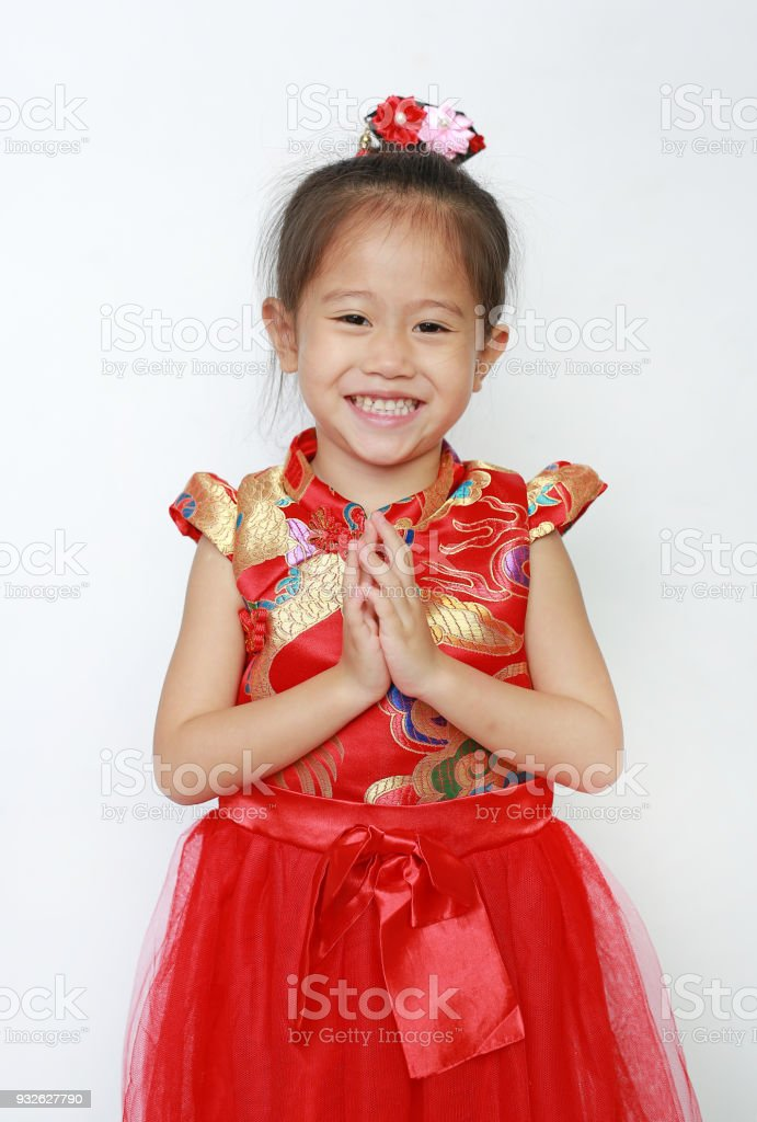 Smiling little Asian girl wearing red Cheongsam with Respect 'Sawasdee' isolated on white background. Happy Chinese new year. stock photo