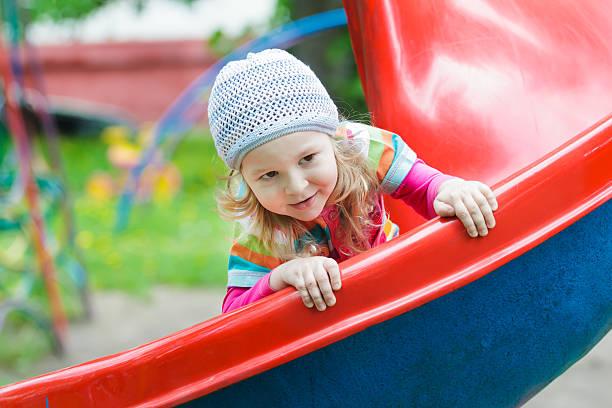 lächelnd kleine blondine mädchen mit rotem kunststoff und rutschen auf dem spielplatz folie - hofkleider stock-fotos und bilder