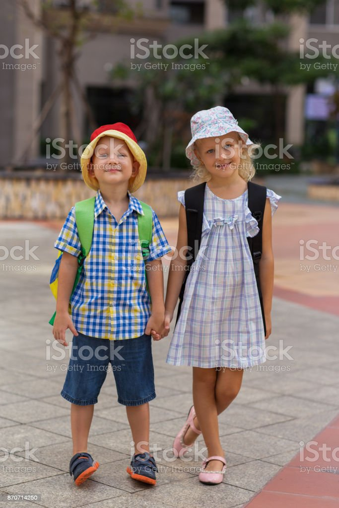 Smiling Little Boy and Girl Holding Hands Outdoors stock photo