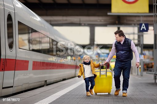 Smiling little boy and his father waiting express train on railway station platform. Travel, tourism, winter vacation and family concept. Man and his son together.
