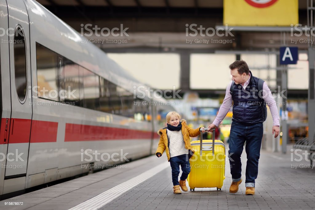 Smiling little boy and his father waiting express train on railway station platform stock photo