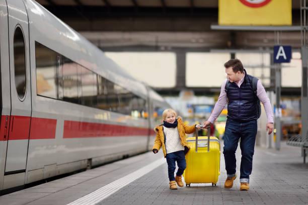 lächelnden kleinen jungen und seinem vater schnellzug auf bahnhof bahnsteig wartend - bahn reisen stock-fotos und bilder