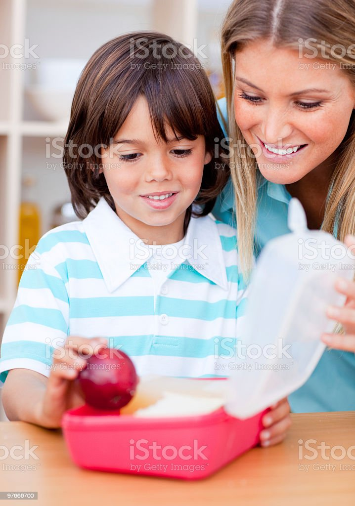 Smiling little boy and his mother preparing school lunch stock photo