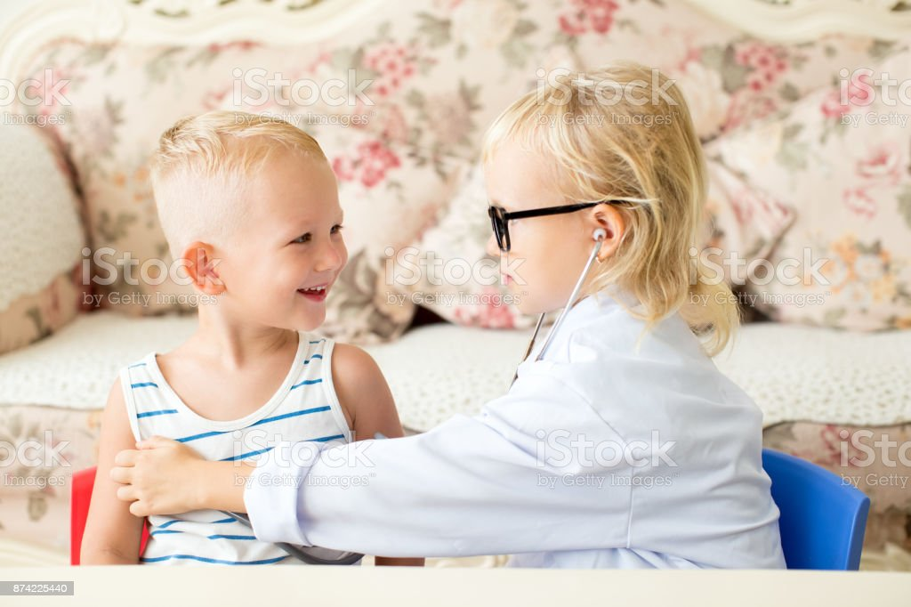 Smiling little boy and serious girl playing doctor stock photo