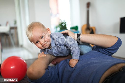 649431568 istock photo Smiling little boy have fun with his father in living room 1185882249