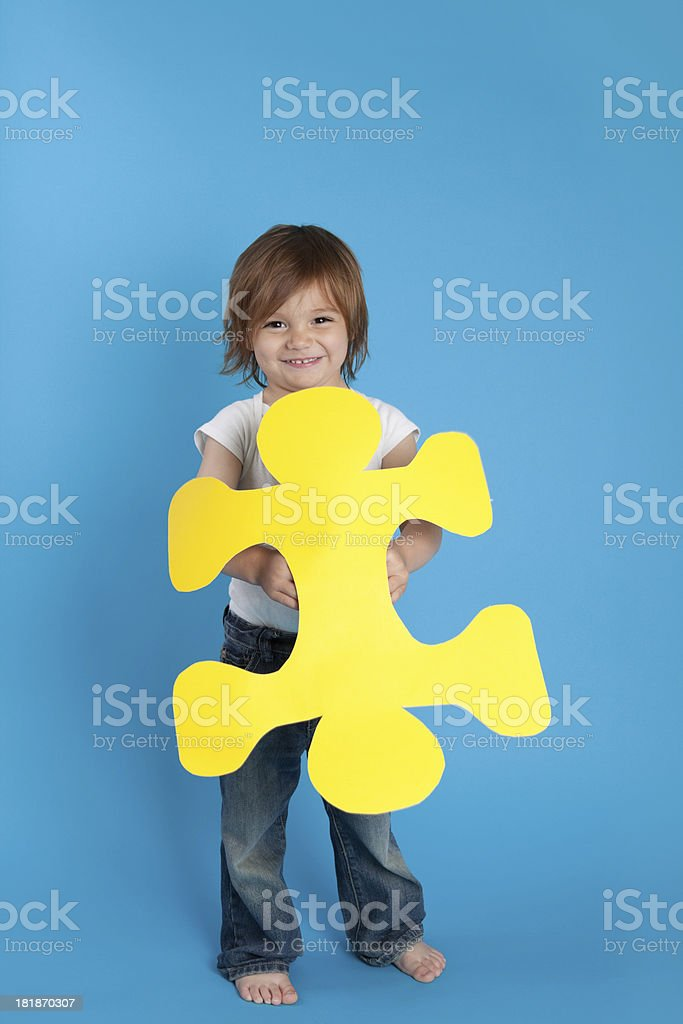 Smiling Little Boy Holding  Large Yellow Puzzle Piece stock photo