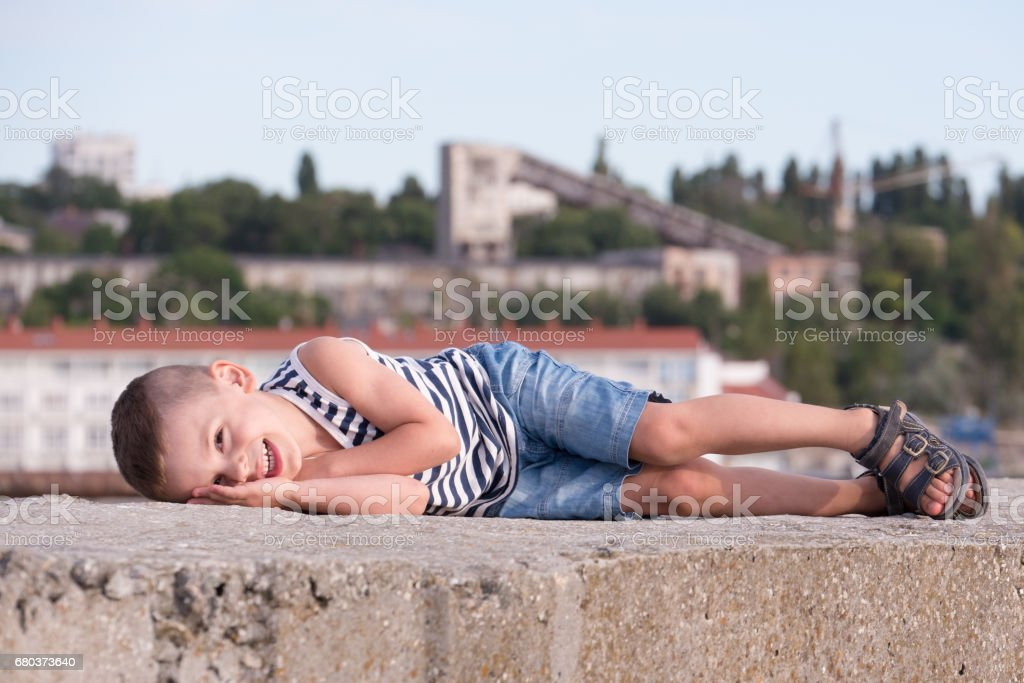 smiling little boy lies on a concrete block on a background of port buildings royalty-free stock photo