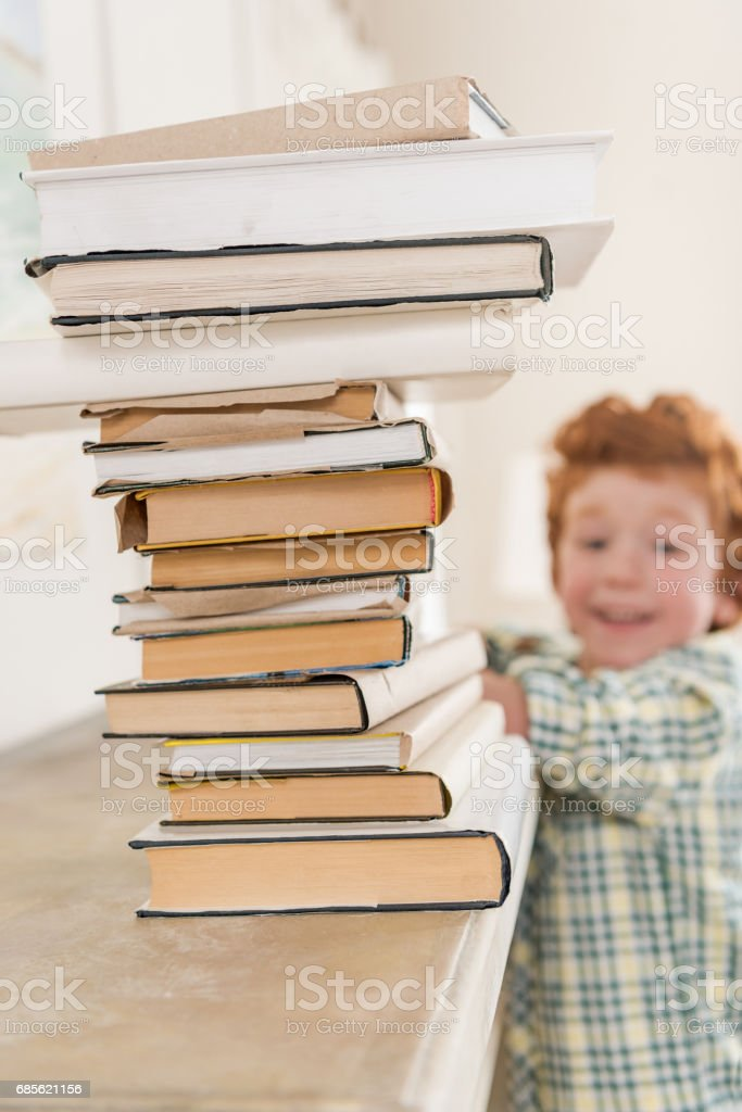 smiling little boy looking at pile of books, focus on foreground foto de stock royalty-free