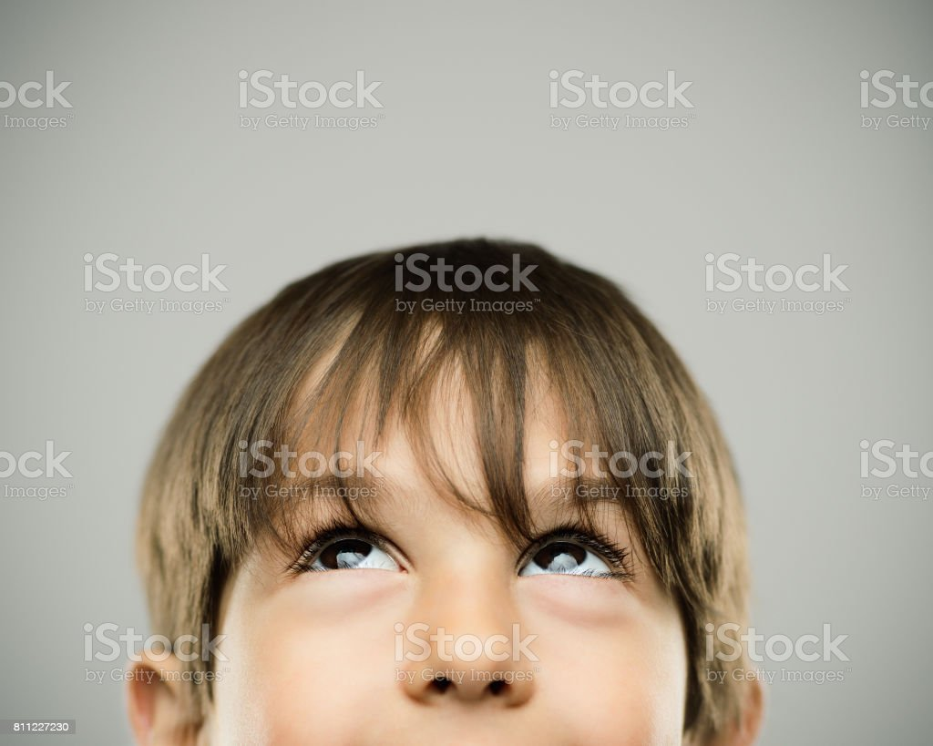Smiling little boy looking up stock photo