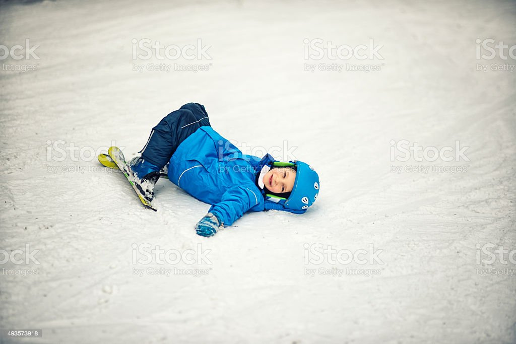 Smiling little boy lying on snow after crashing during lesson stock photo