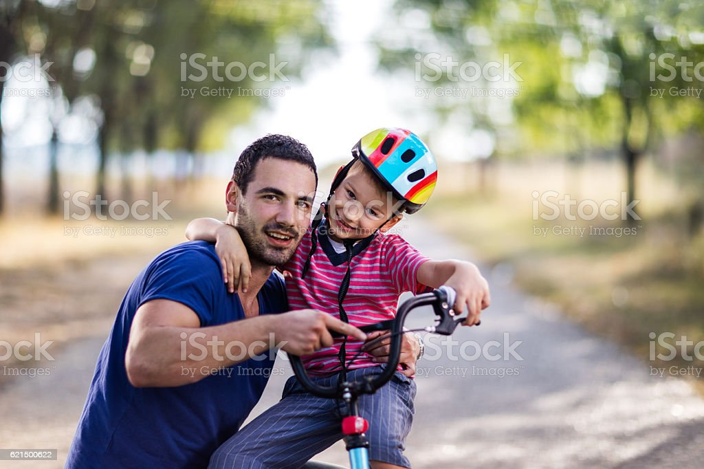 Smiling little boy on bike embracing his father. foto stock royalty-free