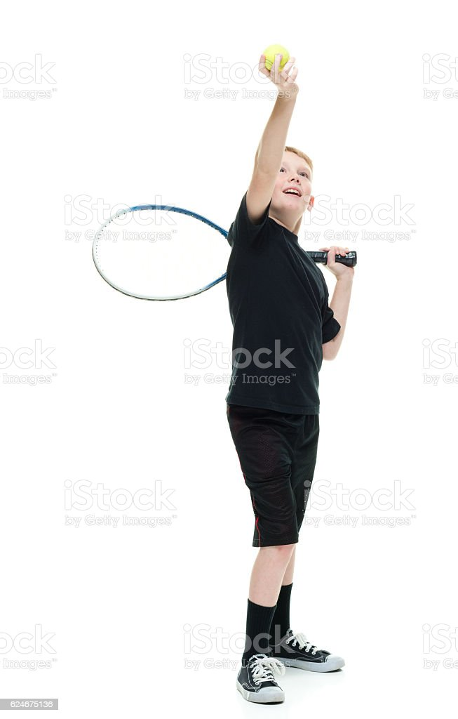 Smiling little boy playing tennis ball stock photo