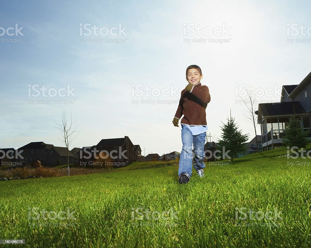 Smiling little boy running on a grass field royalty-free stock photo