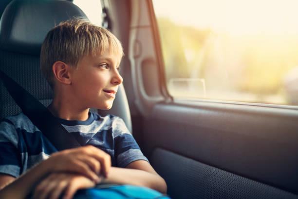 Lächelnde kleine Junge sitzt Auto im Kindersitz. – Foto