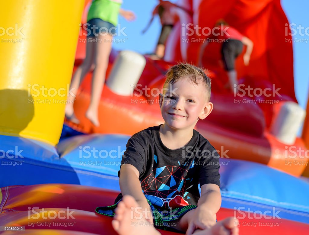 Smiling little boy sitting on a jumping castle stock photo