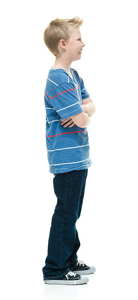 Smiling little boy standing with arms crossed stock photo